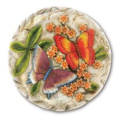 Butterfly Stepping Stone. A pair of vivid butterflies frolics amongst lush foliage, enlivening a bas-relief stepping stone with glowing colors and romantic sentiment.