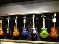 Guitar Wall. one big frame around them all, plus fabric/plush backing to protect the backs.  nice touch