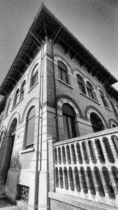 The Scuola Elementare, designed by Arnaldo Fuzzi in This building provides an example of repetition of architectural elements as decoration, both for windows and the fence. Repetition Examples, Black White Photos, Black And White, Architectural Elements, Atrium, Fence, Louvre, Windows, Architecture