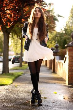 White dress, black stockings, leather jacket and boots.