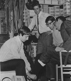 Employee Johan Cruyff (Dutch & Barcelona football legend) helping someone try on shoes at a sports store when he was a teenager.