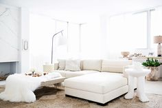 Bright white living room with a large sectional sofa, and faux fur throw and a marble fireplace
