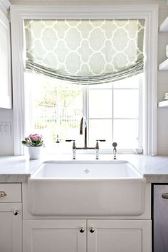 We love everything in this kitchen from the white farmhouse sink to the marble counters and geometric shade.