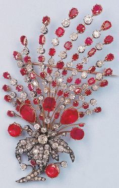 A magnificent silver, gold, diamond and ruby brooch, 19th century. The articulated brooch centre designed as a stylised amaryllis set with old-cut diamonds, surrounded by radiating sprays set with old-cut diamonds and rubies or red stones, mounted in silver and gold.