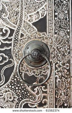 Native Thai style wood carving on temple door....