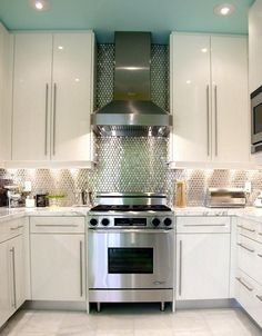 cook with an aqua celing, silver backsplash & high gloss white cabinets