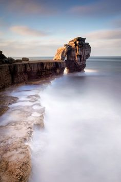 An autumnal sunrise at Pulpit rock on the Isle of Portland with the full force of the English Channel waves reduced to a milky blur by a long exposure.