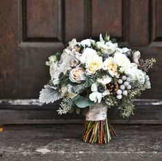 I like the use of winter accents in this bouquet - am thinking if we replace the white roses with a dark purple flower for the brides bouquet it might tie the wedding and the Christmas theme of the room together.