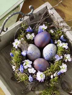 Twiggy wreath with moss, feathers, lavender flower, blue to purple eggs in a tray...