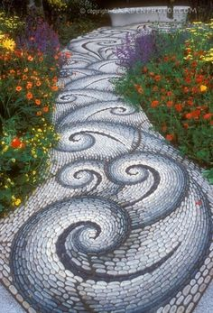 Stone walkway in the garden leading to a garden bench, with twists and twirls in pattern, along vibrant flower garden of red, yellow, orange, and purple, inlcuding Geum, Achillea, Salvia perennial plants. Creates feeling of movement and excitement. Beautiful one day.