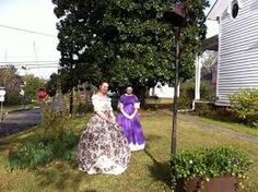 Pilgrimage time at Gregg-Hamilton House in Aberdeen, Mississippi.  These southern belles stand beside the old plantation bell and syrup kettle.