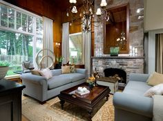A soaring stone fireplace is an impressive and rustic focal point in this living room. To reduce the scale of the stone and add interest, a long mirror is placed above the mantel. Candice also uses the fireplace as a jumping off point for the room's palette, by selecting the hues of sage, stone, taupe and caramel from the fireplace stones.