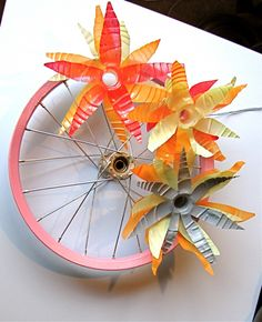 holy shit! bicycle tire + flowers made from empty plastic bottles with tops cut off, triangles cut out from top, spray painted, then stacked like so and tied to bike wheel.  LOVE THIS for outside.