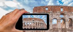 Woman hand with smartphone taking a picture of Colosseum in Rome.