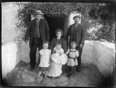 Family with grandfather posing for photographer outside their cottage home. Taken sometime during the late 1800s with a glass plate camera. It is somewhere in County Leitrim, Ireland.