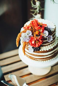 A naked carrot cake topped with fresh fall flowers by Mayflour Confections.
