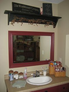 Framed mirror and shelf above.