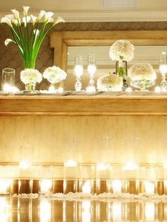 White flowers on a table: pretty. White flowers on a table, bathed in candlelight: really pretty, and romantic. Get creative with the candleholders; instead of just plain votives, go with fluted ones and cylinder vases.