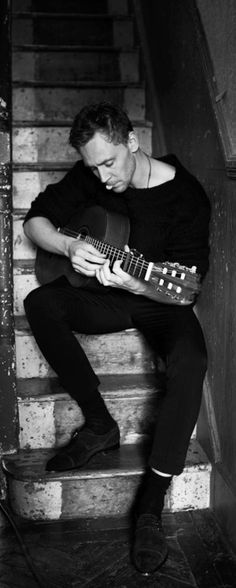 Things that can make a hot Tom Hiddleston even hotter: Long sleeve black sweater, CHECK. Playing acoustic guitar, CHECK.