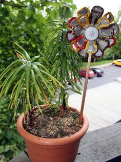 Bottle Cap Pinwheel Flower | AllFreeHolidayCrafts.com Isn't this Bottle Cap Pinwheel Flower pretty? It's almost hard to believe this lovely garden decoration is made out of recycled materials like drink tops, a tin can lid and an old chopstick! If you've always wanted to experiment with bottle cap crafts, this is a great project to try. Find out how to make this cool recycled craft with this easy spring tutorial.