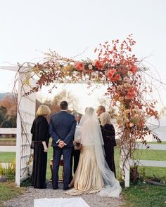 A white arbor decorated with seasonal flowers fit into the scenic backdrop of this outdoor fall wedding in the Hudson Valley. See more of Hanna and Jimm's wedding day by following the link!