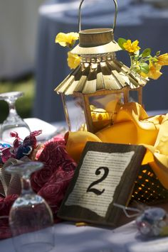 centerpiece: flowers, roses, lantern, fabric and burlap. Table numbers: old fence board cut and book page printed on number pasted on