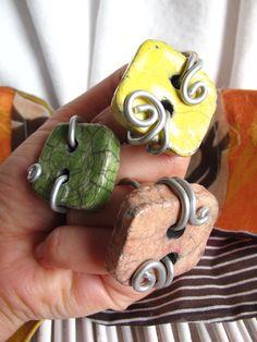 Anelli quadrati in ceramca raku, quadrati, lavorati a mano intrecciati con un filo di metallo color argento che crea un motivo particolare. Anche l'intreccio del filo e' fatto a mano e rende l'oggetto unico.