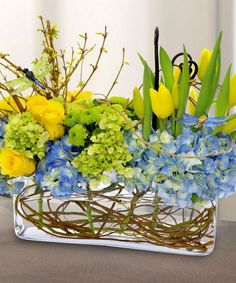 decorate glass vases spring shaped low vase spring garnishment yellow tulips roses and blue hydrangea forsythia branches visible