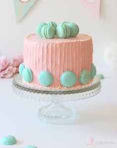 Zitronentorte gefüllt und umhüllt mit einer weißen (rosa) Schokoladencreme und geschmückt von zitronigen Macarons. <3