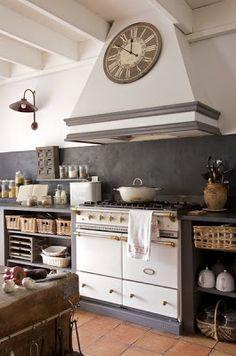 BOISERIE & C. Love the gray stone backsplash with the white range and funky rangehood