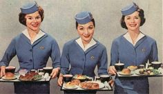 Pan Am stewardesses of the early 1960s holding trays of airline dinners - economy class.