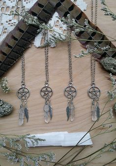 """Small star (pentacle) charms complete with a wire wrapped Quartz crystal and metal feather charm. Quartz is a power stone. It has been called the """"Universal Crystal"""" because of its many uses. It enhan"""