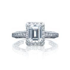 Graduated round diamonds and tapered rows of pavé set diamonds lead up to a brilliant emerald cut center diamond. With one row of diamond bloom enhancing the center diamond, this ring will capture everyone's attention. #Tacori #TacoriRing #engagementring #emeraldcut #emeraldring #DreamRing