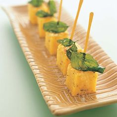 Bite-size canapé cubes of warm polenta with Parmesan and prosciutto are topped with a flash-fried micro-basil leaf for zest. Tray, Tilson Design Works