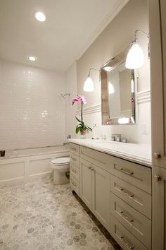 Heights, Houston Bungalow Remodeled! Guest bathroom with hexagon tiling. Very common in historic homes but here it is used at a larger scale offering a slightly more modern spin on a tried-and-true favorite. Bright beveled subway tile. Marie Flanigan Interiors www.marieflanigan.com