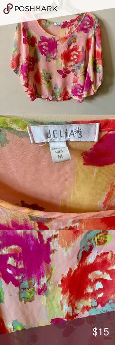 Delia's Medium Pink Multicolored Floral Blouse This is a lovely Delia's top. It is a light pink with a light green, purple, red, white, yellow, and blue formal watercolor pattern. Great addition to your summer wardrobe!  Size medium. Material is 100% polyester. Delia's Tops Blouses