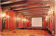 """Hearst Theatre, San Simeon CA. THE THEATRE — In La Casa Grande the private projection room seated 100 people. The latest movies were shown following dinner each night. The room is panelled with antique red brocade and illuminated by torches held in the hands of caryatides, carved female figures. The host habitually occupied the left hand seat in the front row, with a telephone close at hand, in constant touch with his newspaper empire.""""  Postcard ©P. C. Jones"""