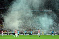 spain game: Smoke evelopes the pitch as another flare is set off in the stand