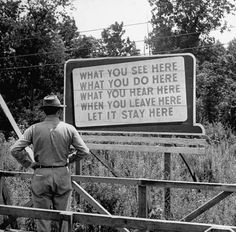 A billboard at the Oak Ridge Facility, in Oak Ridge, Tenn., which warned workers there to maintain silence and secrecy about what they were working on: the development of the atomic bomb as part of the Manhattan Project. The photograph was taken in August 1945.