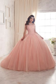 Dazzle the room in a House of Wu Quinceanera Dress Style Number 26844 during your Sweet 15 party or any formal event. Glimmering in showcase fashion is this gorgeous Quinceañera gown with a densely sequined and beaded portrait neckline and off-the-shoulder bodice. The full ball gown skirt splays down in brilliant displays of beaded and sequin tulle layers, with a sparkle tulle layer underneath. Complete with lace-up back.  House of Wu Quinceanera Collection Spring 2017 Colors: Rose Petal…