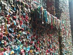 """""""A visit to Seattle's Gum Wall becomes an interactive art experience.  For those of you not familiar with this odd attraction it's located in Post Alley just off of the famous Pike Place Market. As you follow the cobble stone street it leads you to one of the city's quirkiest sites, the Market Theater Gum Wall. Here is where you will find the chewy remains of thousands upon thousands of gum wads all stuck to the wall in a fascinating display of gooey glory.  Since 1993"""""""
