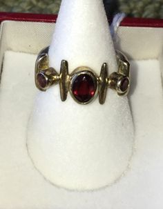 Artisan jewelry ring. Three garnets set gold and silver Etruscan setting. Size 7.