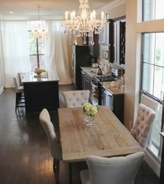 Love the color palette in here. Dark cabinets with white walls, curtains, etc...