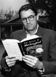 "Gregory Peck reading his own copy of ""To Kill a Mockingbird"" while on set, 1962."