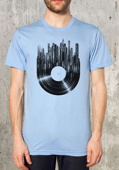 This music t-shirt features an old vinyl record that breaks up and melds into a detailed cityscape! This urban styled t-shirt makes a great