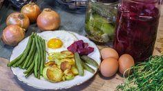 Auf einem Teller sind Bohnen, Bratkartoffeln, Spiegelei und saure Gurken angerichtet.