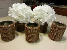 Flower cans!! All you need is a soup can, rope, and hot glue. Then put whatever big flower you want inside!