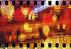 Glitch Lights by MANDRAGUZZLE. Abstract glitchy spherical orange and red lights on film with sprockets. #abstract #glitch #light #loom #lomography #photo #photography #sprocket #film #red #orange #redscale