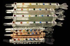 Jeder Stab wird in Indien aus hochwertigen Edelsteinen und indischen Silber handgefertigt.  Neben einem Edelsteinschaft haben die Stäbe auch einen Silberstreifen an der Seite, der wiederum mit sieben farbigen Steinen verziert ist. Diese sieben Steine repräsentieren die sieben Chakras.  Außerdem sind die Stäbe an derem Ende mit einem Edelsteinngel verziert.  Da diese Stäbe handgefertigt werden, kann deren j