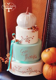 Turquoise and orange Thanksgiving cake topped with a hand painted pumpkins and crab apples.